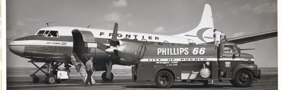 Pueblo Memorial Airport, old black and white photo of an old Frontier passenger plane getting refueled on the runway.