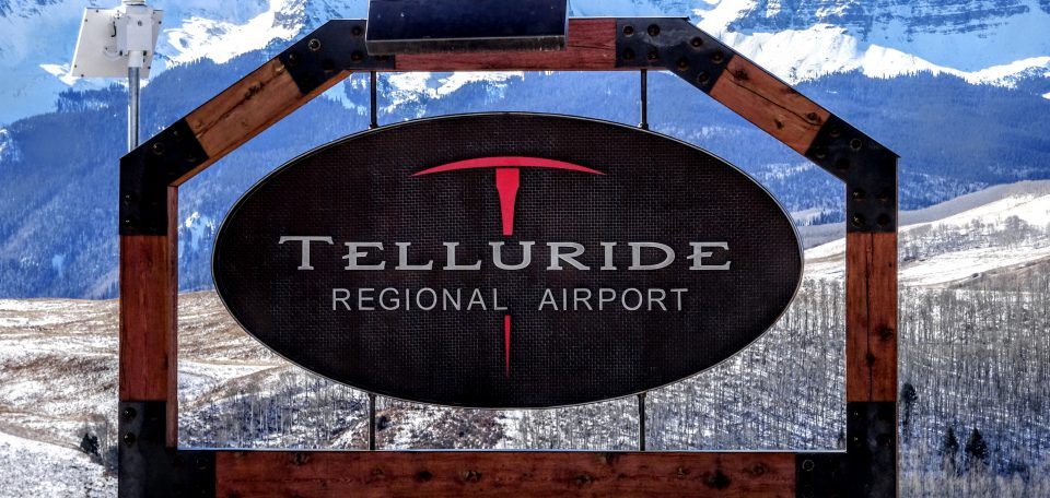 Telluride Regional Aiport Sign with mountains and a field behind.