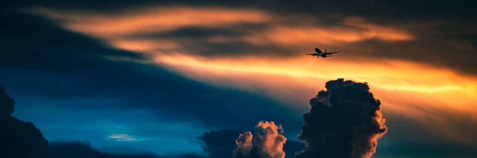 Cape Fear Regional Jetport, a jet flying with clouds and colorful skies.
