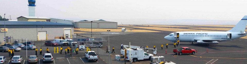 Lewiston-Nez Perce County Regional Airport. View of building, vehicles parked and an passenger jet on the right.