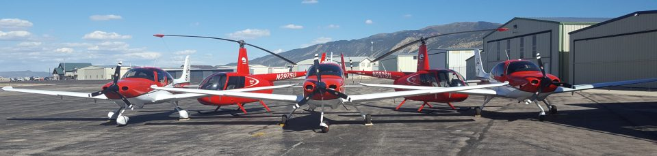 Cedar City Regional Airport. Three red and white airplanes and two red helicopters in a row on the tarmac.
