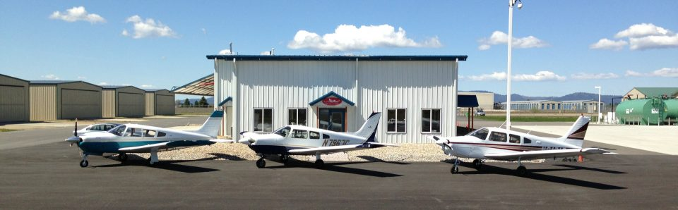 Deer Park Air Center building with 3 small aircraft parked in front in a row.