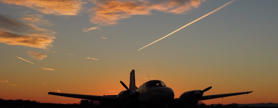 Warrenton-Fauquier Airport contrails and orange sky behind a plane silhouette on the runway.