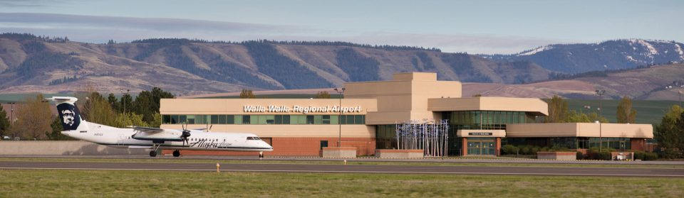 Walla Walla Regional Airport terminal building with a jet out front and mountains behind.