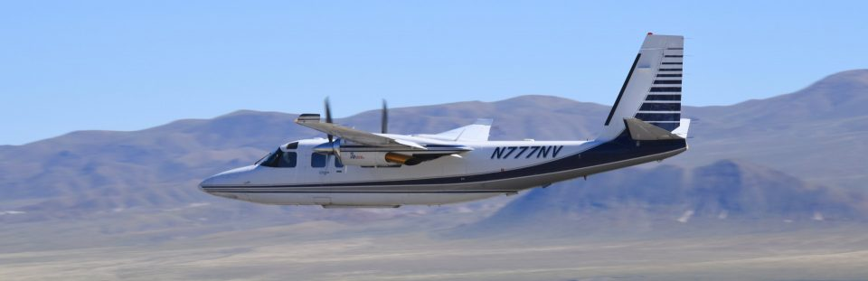 The Carson City Airport in Carson City Nevada, photo of a two prop plane in flight.
