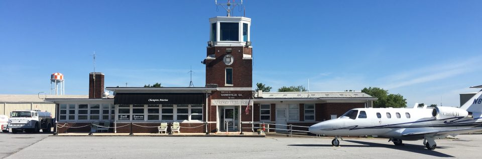 Lee Gilmer Memorial Airport terminal from the runway side with a Citation jet out front.