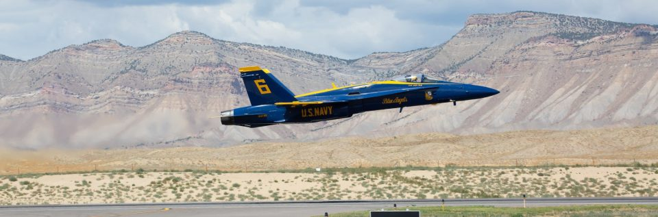 Grand Junction Regional Airport with a Blue Angel jet flying over the runway.