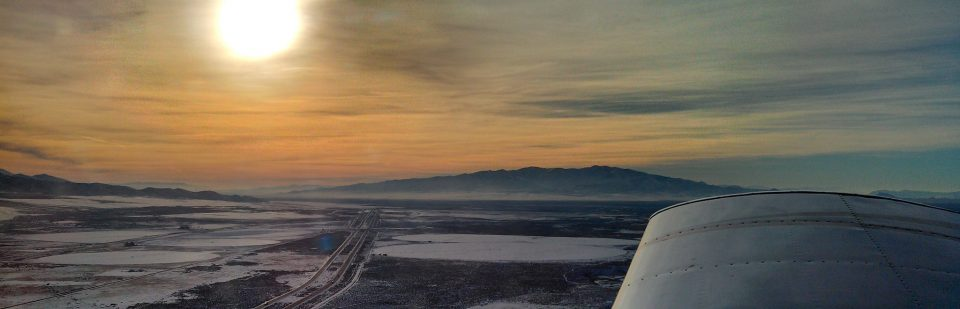 The Winnemucca Municipal Airport stock photos of a view from a plane over the airport with the sun in the background.