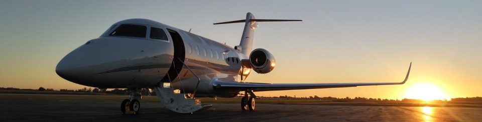 Allen County Airport jet on the runway with the sun setting behind