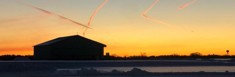 Wausau Downtown Airport at sunset with contrails and snow